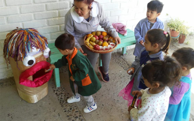 En la entrada del recinto de Olmué, la funcionaria encargada de recibir a los niños y niñas, junto al personaje, invita a los párvulos a intercambiar la golosina por un rico snack saludable.