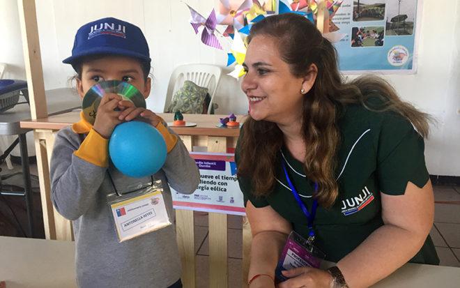 """Arica, (@JUNJI_Arica). Curiosidad y asombro mostraron las niñas y niños que interactuaron y recorrieron los 26 stands implementados en la Universidad de Tarapacá, a fin de celebrar la Semana de la Ciencia y la Tecnología en Arica. Dos de los stands de esta VI Feria Infantil exhibieron los proyectos científicos de los jardines infantiles """"Dumbo"""" y """"Avioncito"""" de la JUNJI. En ellos, las educadoras de párvulos Daiffa Habib e Isabel Palleres fueron las encargadas de mediar experiencias educativas que buscaban desarrollar el pensamiento crítico en niñas y niños, quienes aprendieron de la energía eólica a través de materiales reciclados, y exploraron con arena mágica. Cabe mencionar que la VI Feria Infantil, organizada por el PAR Explora Conicyt, es una muestra de experiencias científicas en las áreas de ciencias naturales, ciencias sociales, ingeniería y tecnología, está orientada a niñas y niños que cursan educación parvularia, educación especial y primer ciclo de enseñanza básica. Esta iniciativa muestra a la comunidad los trabajos desarrollados dentro del aula, incentivando el intercambio de experiencias y la formación científica."""